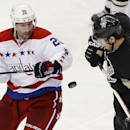 Pittsburgh Penguins' James Neal (18) and Washington Capitals' Troy Brouwer (20) try to control the puck as it flies by during the third period of an NHL hockey game, Tuesday, March 11, 2014, in Pittsburgh. The Penguins won 2-0 The Associated Press