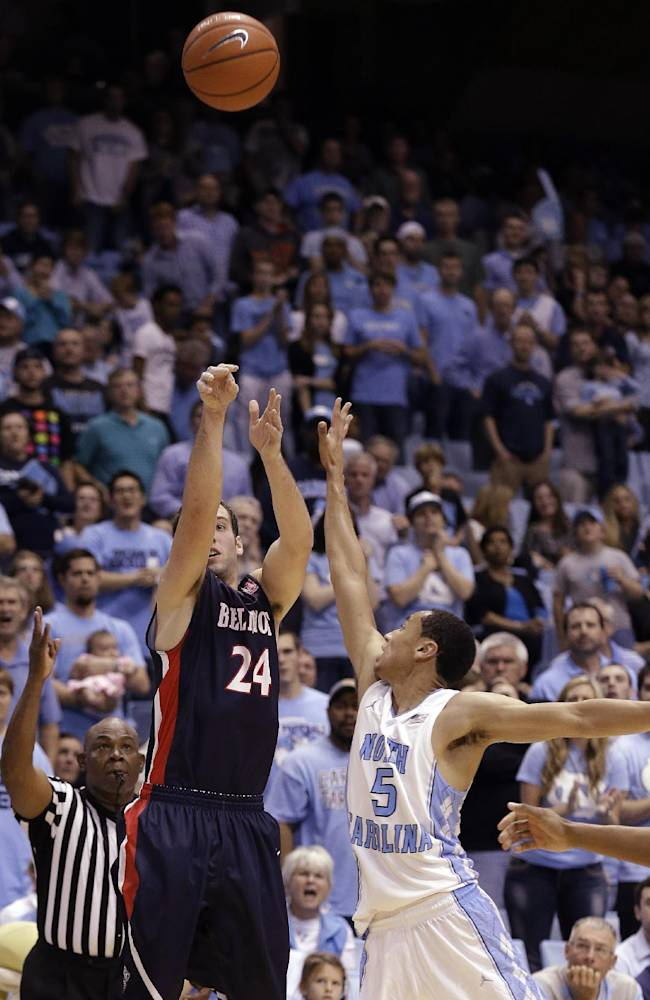 North Carolina's Marcus Paige (5) tries to block as Belmont's J.J. Mann (24) shoots a three-point basket during the second half of an NCAA college basketball game in Chapel Hill, N.C., Sunday, Nov. 17, 2013. Belmont won 83-80