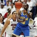 UCLA's Shabazz Muhammad (15) passes under pressure from Arizona's Nick Johnson (13) during the first half of an NCAA college basketball game at McKale Center in Tucson, Ariz., Thursday, Jan. 24, 2013. UCLA won 84-73. (AP Photo/John Miller)