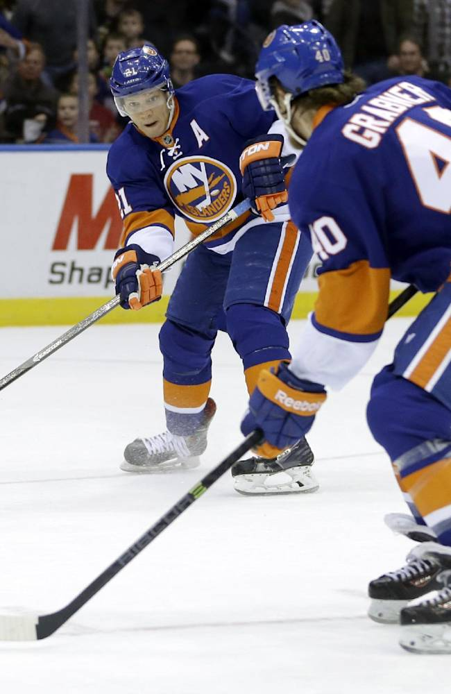 New York Islanders' Kyle Okposo, left, passes to Michael Grabner before scoring during the second period of the NHL hockey game against the Boston Bruins, Monday, Jan. 27, 2014, in Uniondale, New York