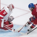 Montreal Canadiens' David Desharnais, right, slides in on Detroit Red Wings goaltender Jimmy Howard during third period NHL hockey action in Montreal, Tuesday, Oct. 21, 2014 The Associated Press