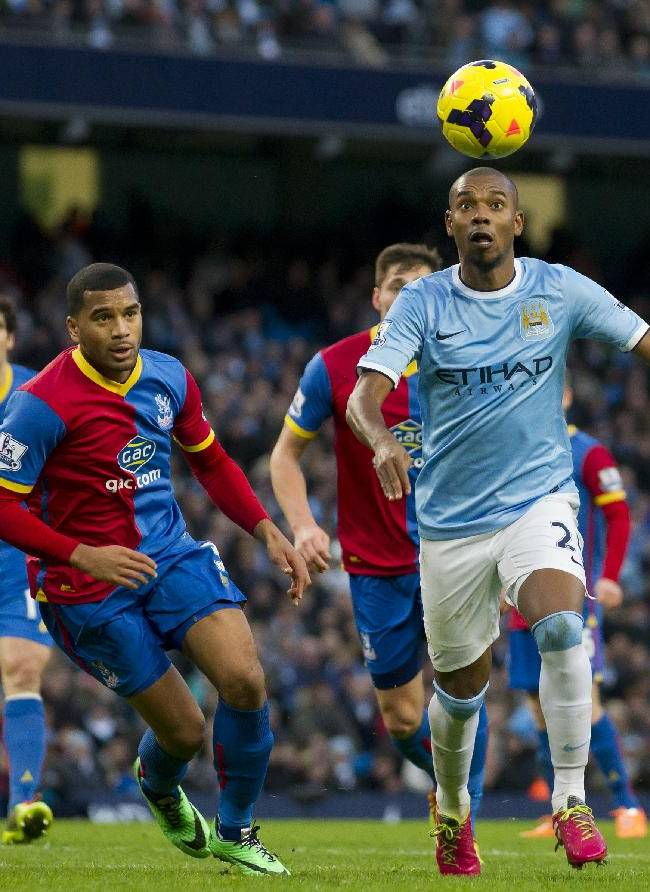 Manchester City's Fernandinho, right, keeps the ball from Crystal Palace players including Adrian Mariappa, centre left, during their English Premier League soccer match at the Etihad Stadium, Manchester, England, Saturday Dec. 28, 2013