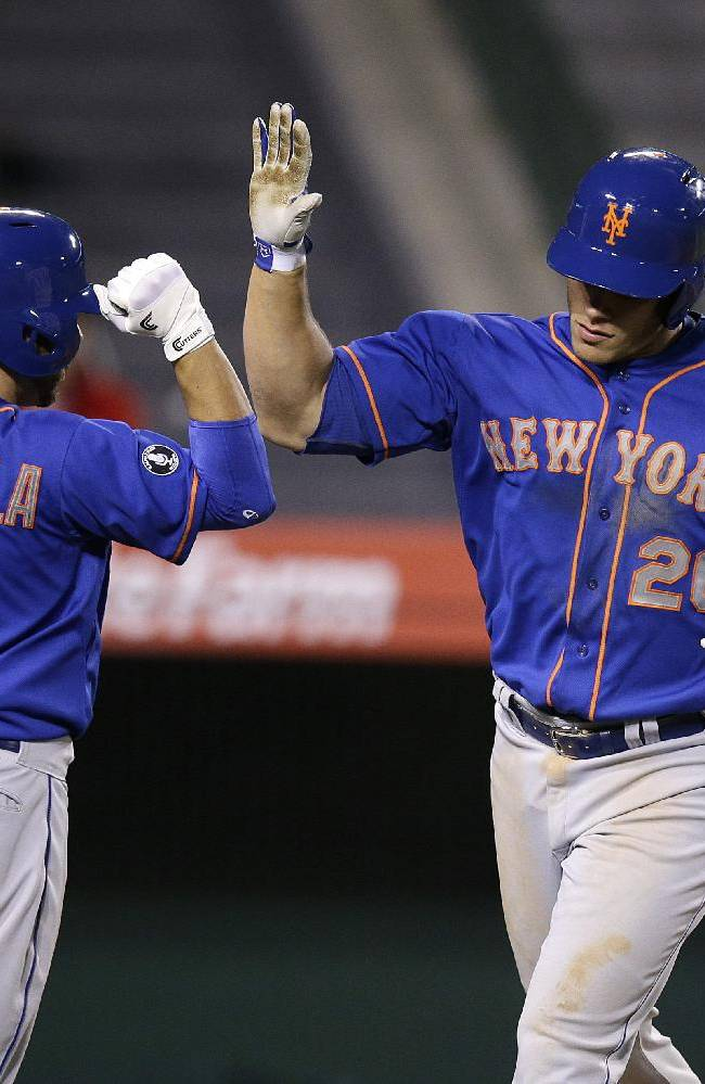 New York Mets' Anthony Recker (20) celebrates his home run with Omar Quintanilla during the 13th inning of a baseball game against the Los Angeles Angels on Saturday, April 12, 2014, in Anaheim, Calif