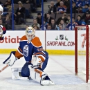New York Rangers' Martin St. Louis (26) tries to screen Edmonton Oilers goalie Ben Scrivens (30) during first period of an NHL hockey game in Edmonton, Alberta, Sunday, Dec, 14, 2014 The Associated Press