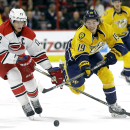 Carolina Hurricanes' Eric Staal (12) and Nashville Predators' Calle Jarnkrok (19), of Sweden, chase the puck during the first period of an NHL hockey game in Raleigh, N.C., Tuesday, Dec. 2, 2014 The Associated Press