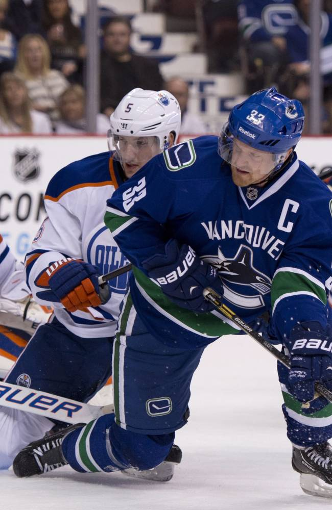 Vancouver Canucks center Henrik Sedin (33) tries to get a shot past Edmonton Oilers goalie Devan Dubnyk (40) and defenseman Ladislav Smid (5) during the first period of an NHL hockey game in Vancouver, British Columbia, Saturday, Oct. 5, 2013