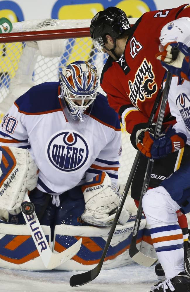 Edmonton Oilers goalie Devan Dubnyk, left, makes a save on a shot from Calgary Flames' Lee Stempniak, center, as Jeff Petry tries to pull him away during second period NHL hockey action in Calgary, Alberta