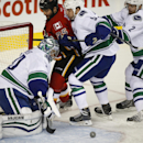 Vancouver Canucks' Dan Hamhuis, right, and Derek Dorsett, center, push Calgary Flames' Brandon Bollig, second from left, away from goalie Ryan Miller during first period NHL hockey action in Calgary, Alberta, Wednesday, Oct. 8, 2014 The Associated Press