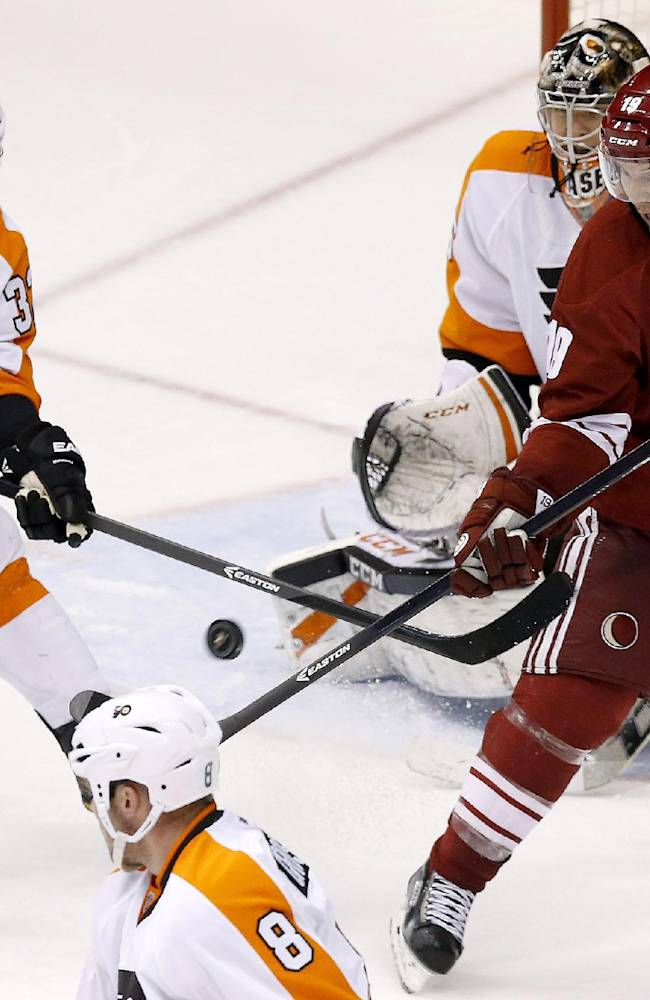 The puck misses hitting Philadelphia Flyers' Nicklas Grossmann (8), of Sweden, in the head as Flyers' Mark Streit (32), of Switzerland, and Phoenix Coyotes' Shane Doan, right, try to get their sticks on the puck in front of Flyers' Steve Mason during the third period of an NHL hockey game Saturday, Jan. 4, 2014, in Glendale, Ariz. The Flyers defeated the Coyotes 5-3
