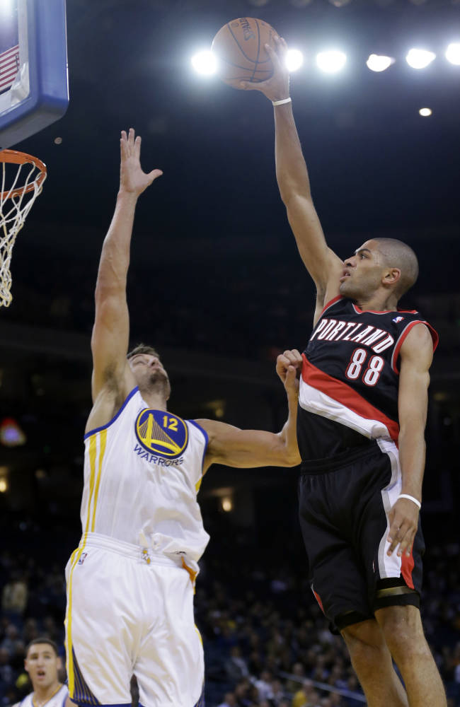 Portland Trail Blazers' Nicolas Batum (88) shoots over Golden State Warriors' Andrew Bogut during the first half of an NBA preseason basketball game on Thursday, Oct. 24, 2013, in Oakland, Calif
