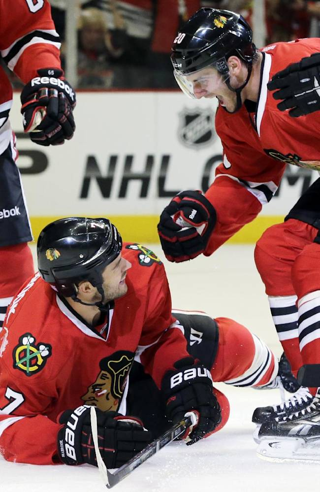 Chicago Blackhawks' Brent Seabrook (7) celebrates with Brandon Saad (20) after scoring a goal during the second period of an NHL hockey game against the Washington Capitals, Tuesday, Oct. 1, 2013, in Chicago