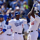 Los Angeles Dodgers' Yasiel Puig, right, points to the sky as Carl Crawford, center, and Adrian Gonzalez look on after hitting a three-run home run during the sixth inning of a baseball game against the Arizona Diamondbacks, Sunday, April 20, 2014, in Los