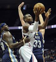 Atlanta Hawks forward Paul Millsap, center, shoots through the defense of Memphis Grizzlies forward Zach Randolph, left, and center Marc Gasol (33), of Spain, during the first half of an NBA preseason basketball game, Sunday, Oct. 20, 2013, in Atlanta. (AP Photo/ John Amis)