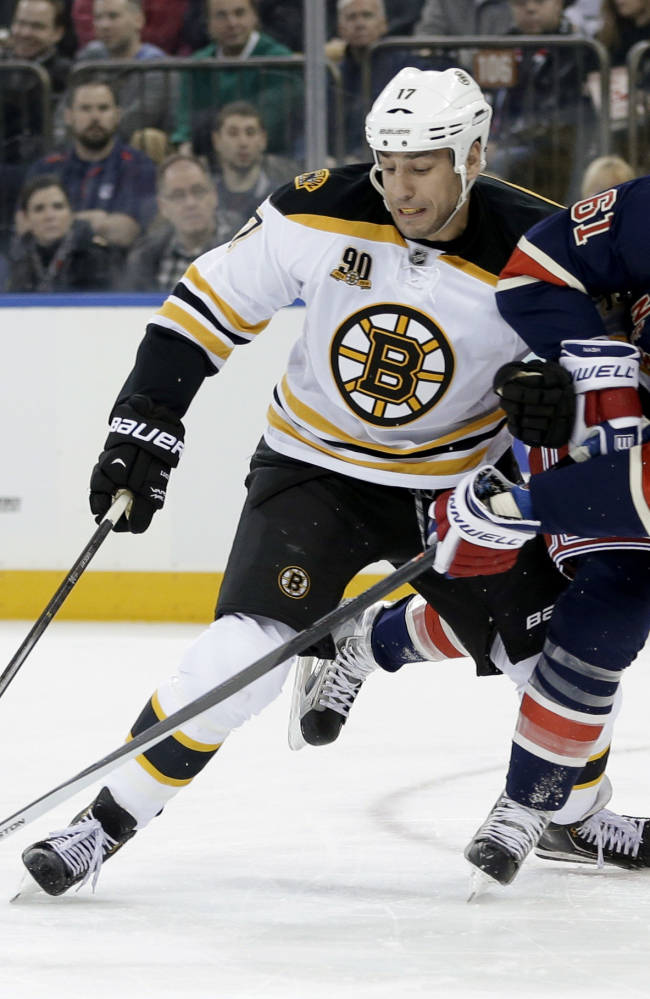 Boston Bruins' Milan Lucic, left, and New York Rangers' Rick Nash battle for position during the first period of an NHL hockey game Sunday, March 2, 2014, in New York