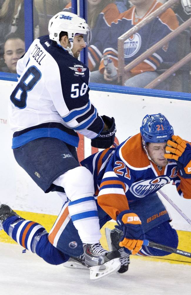 Winnipeg Jets' Eric O'Dell (58) checks Edmonton Oilers' Andrew Ference (21) during the second period of an NHL hockey game in Edmonton, Alberta, on Monday, Dec. 23, 2013