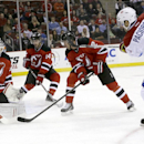 New Jersey Devils goalie Cory Schneider, left, makes a save on a shot by Montreal Canadiens left wing Max Pacioretty, right, as Adam Henrique (14) and Marek Zidlicky (2), of the Czech Republic, defend on the play during the first period of an NHL hockey g