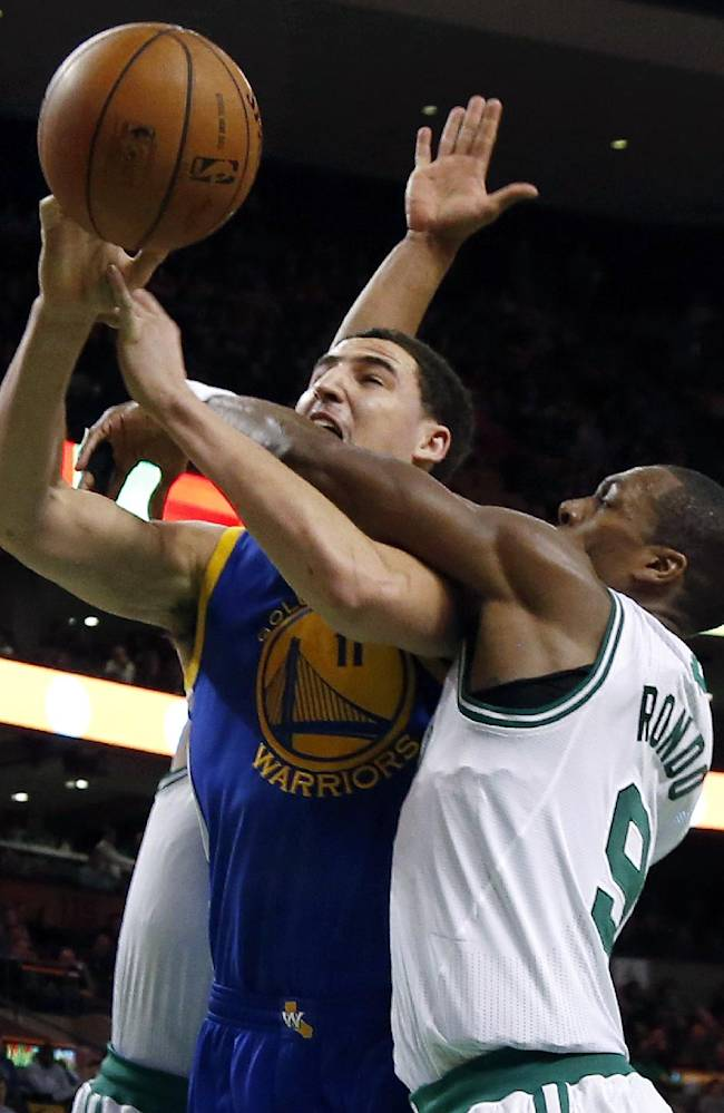 Golden State Warriors guard Klay Thompson (11) is fouled by Boston Celtics guard Rajon Rondo (9) as he goes up for a shot in the second half of an NBA basketball game in Boston, Wednesday, March 5, 2014. The Warriors won 108-88
