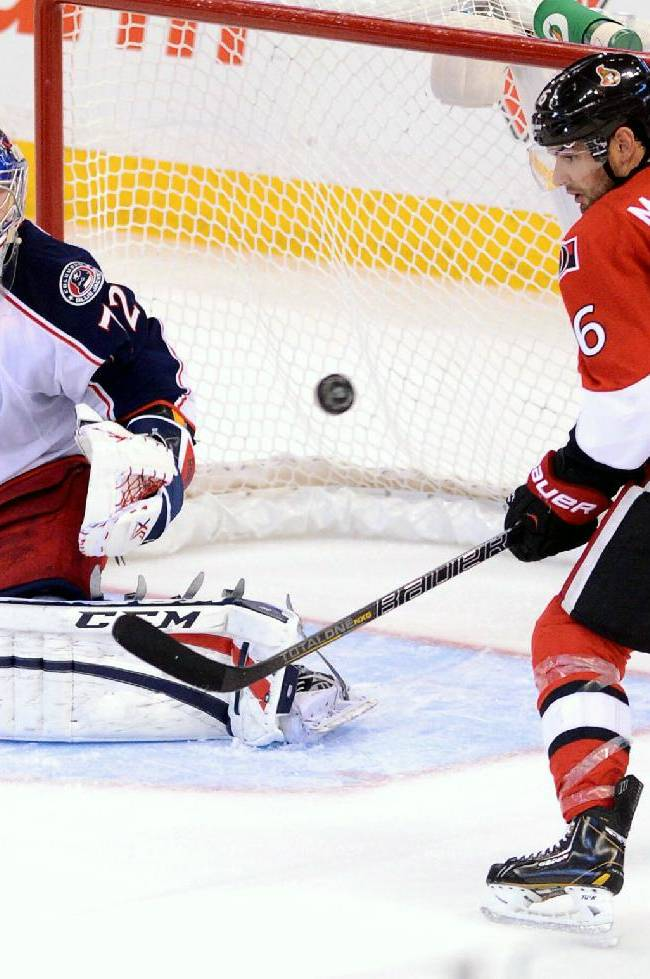 Columbus Blue Jackets' Sergei Bobrovsky keeps his eye on the puck as Ottawa Senators' Clarke MacArthur attempts to score during the third period of an NHL hockey game in Ottawa, Ontario, Sunday, Nov. 17, 2013