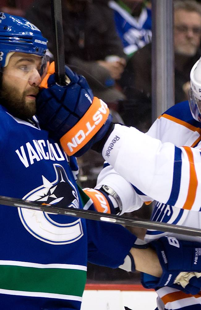 Edmonton Oilers' Anton Belov, left, of Russia, gets his glove in the face of Vancouver Canucks' Chris Higgins during first period NHL hockey action in Vancouver, Canada, Sunday, Jan. 27, 2014