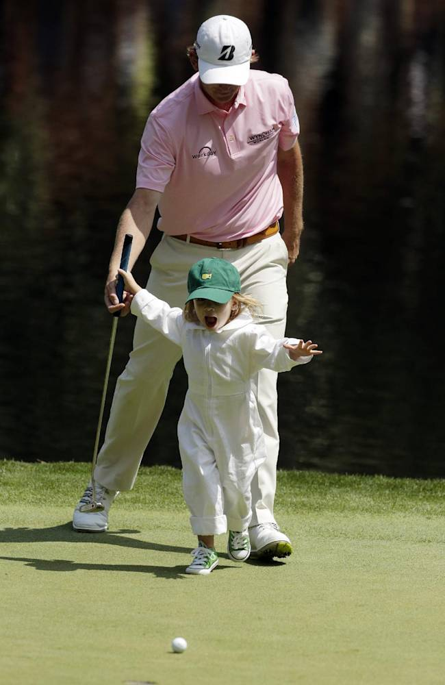 Brandt Snedeker's daughter Lily chases her golf ball on the ninth green during the par three competition at the Masters golf tournament Wednesday, April 9, 2014, in Augusta, Ga