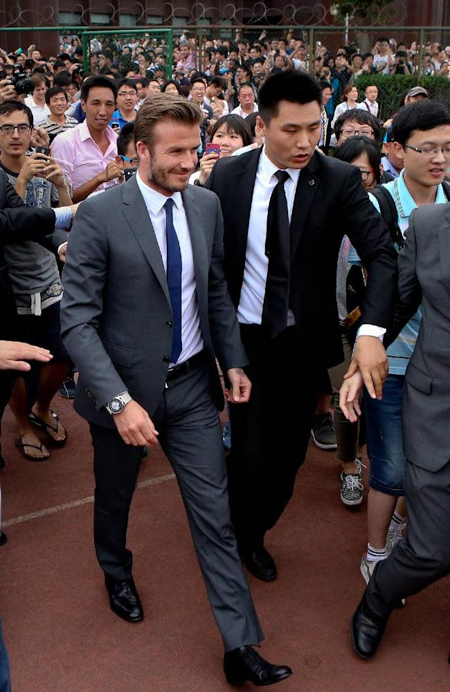 David Beckham walks to meet his fans before a stampede caused by fans storming a security cordon in a university in Shanghai Thursday June 20, 2013. Fans eager to see the soccer superstar stormed a police cordon in a stampede that injured seven people including five security personnel. (AP Photo)