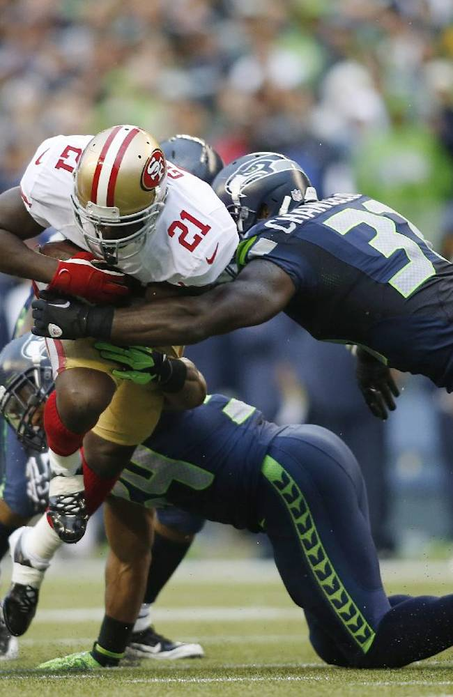 San Francisco 49ers' Frank Gore (21) is tackled by strong safety Kam Chancellor, second from right, in the first half of an NFL football game, Sunday, Sept. 15, 2013, in Seattle