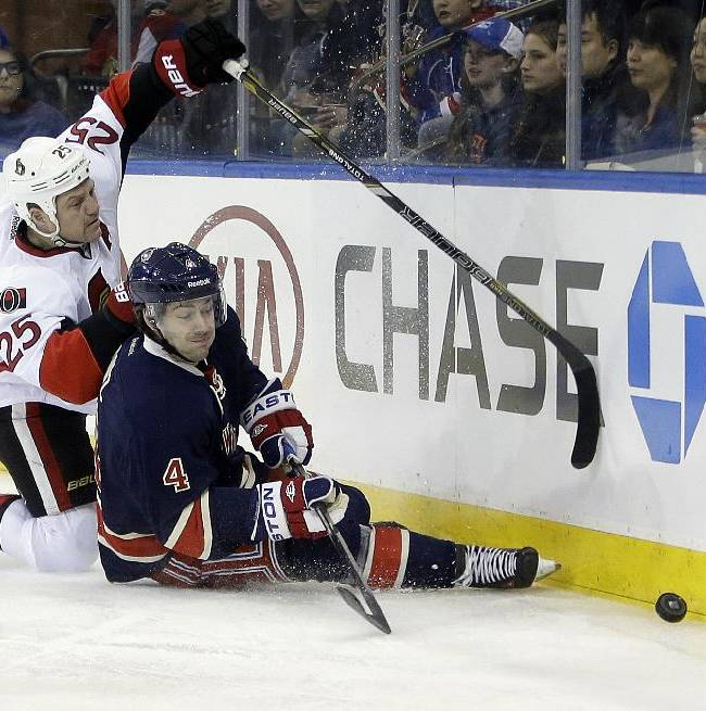 Ottawa Senators' Chris Neil (25) and New York Rangers' Raphael Diaz (4) hit the ice while chasing the puck during the first period of an NHL hockey game Saturday, April 5, 2014, in New York