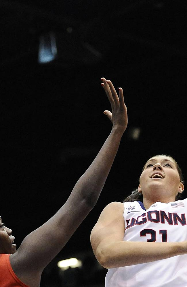 In this Dec. 1, 2013 photo, Connecticut's Stefanie Dolson, right, shoots over Ohio State's Darryce Moore, left, during the first half of an NCAA college basketball game in Springfield, Mass. On Saturday, March 1, 2014, Dolson and fellow senior Bria Hartley will have their names added to the