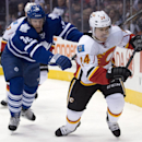 Toronto Maple Leafs defenceman Carl Gunnarsson, left, lays the lumber on Calgary Flames centre Jiri Hudler during first period NHL action in Toronto on Tuesday April 1, 2014. There was no penalty called on the play The Associated Press