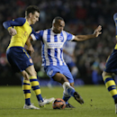Bradford's Billy Knott, centre, competes for the ball with Arsenal's Laurent Koscielny, left, during the English FA Cup 4th round soccer match between Brighton & Hove Albion and Arsenal at the Amex Stadium, Brighton, England, Sunday, Jan. 25, 2015