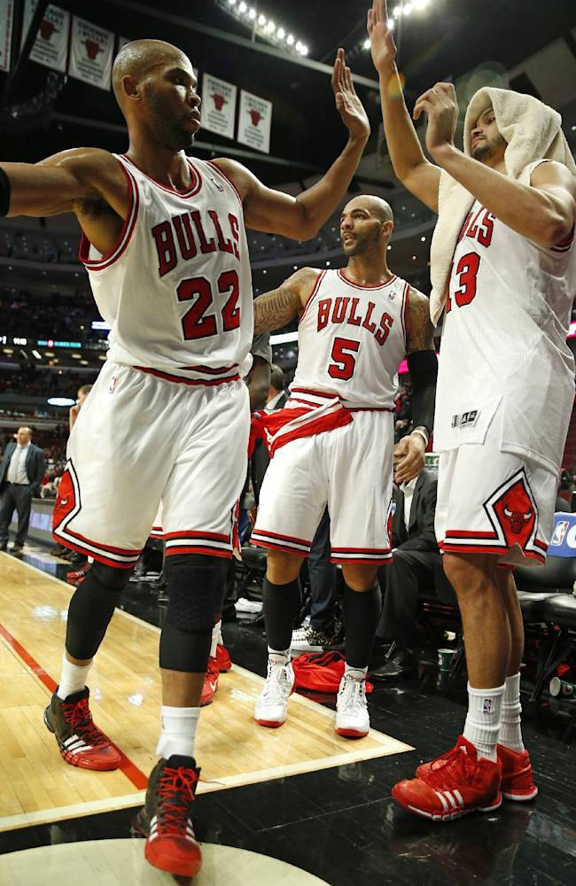 Chicago Bulls forward Taj Gibson (22) celebrates the win against the Miami Heat with forward Carlos Boozer (5) and center Joakim Noah (13) at the end of an NBA basketball game in Chicago, Thursday, Dec. 5, 2013. The Bulls defeated the Heat 107-87