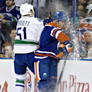 Vancouver Canucks' Derek Dorsett (51) checks Edmonton Oilers' Andrew Ference (21) during first-period NHL hockey game action in Edmonton, Alberta, Friday, Oct. 17, 2014 The Associated Press