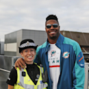 Miami Dolphins' Cameron Wake, right, poses for a picture with a British police officer on her request, after the team's arrival at London's Gatwick Airport, England, Friday, Sept. 26, 2014. The Miami Dolphins will play the Oakland Raiders in an NFL footb