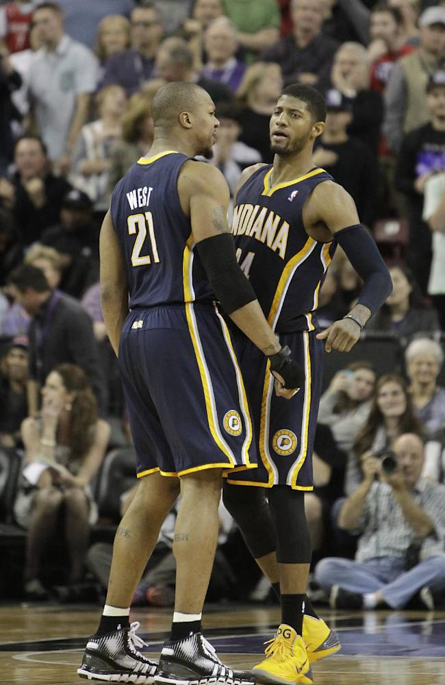 Indiana Pacers forward Paul George, right, gets a chest bump from teammate David West, after he sank a three-point shot and was fouled during the closing moments of an NBA basketball game against the Sacramento Kings in Sacramento, Calif., Friday, Jan. 24, 2014.  George made the free throw that tied the score, sending the game into overtime where the Pacers won 116-111
