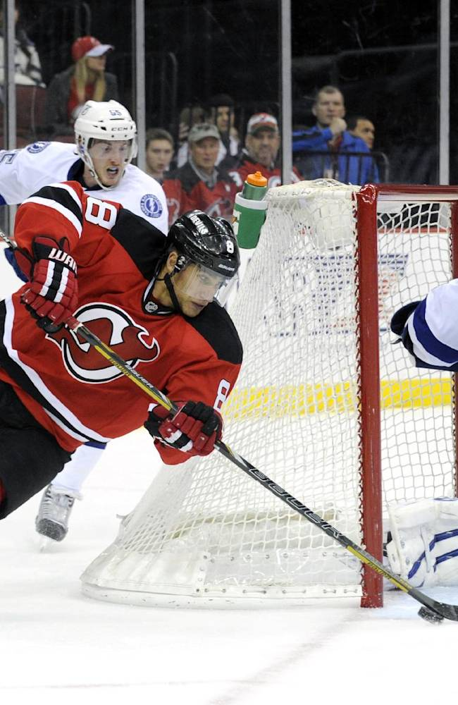 New Jersey Devils, Dainius Zubrus, left, of Lithuania, loses his edge as he skates around the net and attempts a shot against Tampa Bay Lightning goaltender Anders Lindback, of Sweden, during the second period of an NHL hockey game Saturday, Dec. 14, 2013, in Newark, N.J