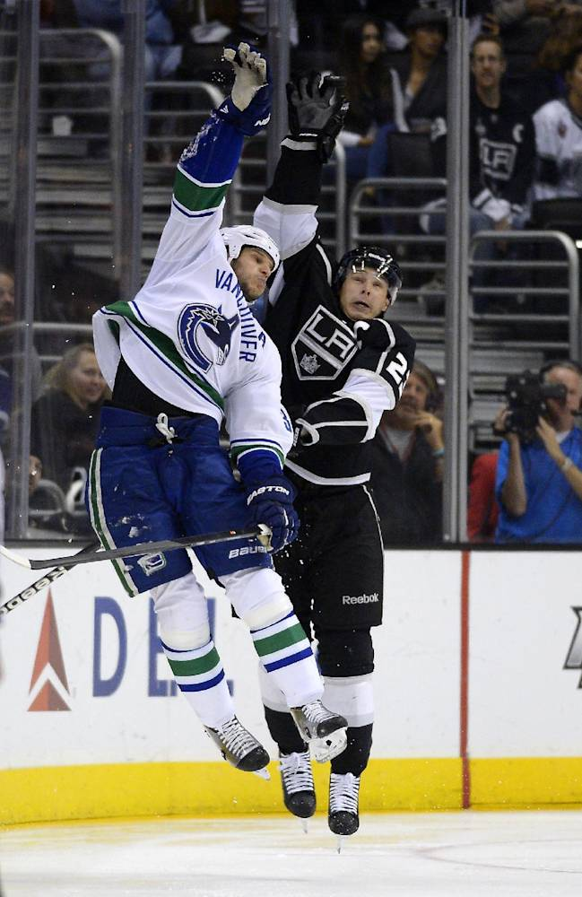 Vancouver Canucks defenseman Kevin Bieksa, left, and Los Angeles Kings right wing Dustin Brown reach for a puck during the third period of an NHL hockey game, Saturday, Nov. 9, 2013, in Los Angeles. The Kings won 5-1