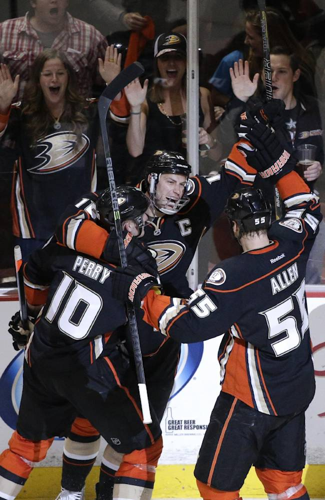 Anaheim Ducks' Ryan Getzlaf (15) celebrates his goal with Corey Perry (10) and Bryan Allen (55) during the first period in Game 2 of the first-round NHL hockey Stanley Cup playoff series against the Dallas Stars on Friday, April 18, 2014, in Anaheim, Calif