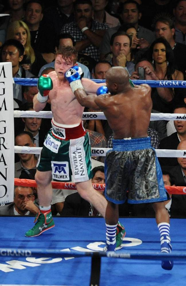 In this photo provided by the Las Vegas News Bureau, Floyd Mayweather Jr., lands a punch to the face of Saul