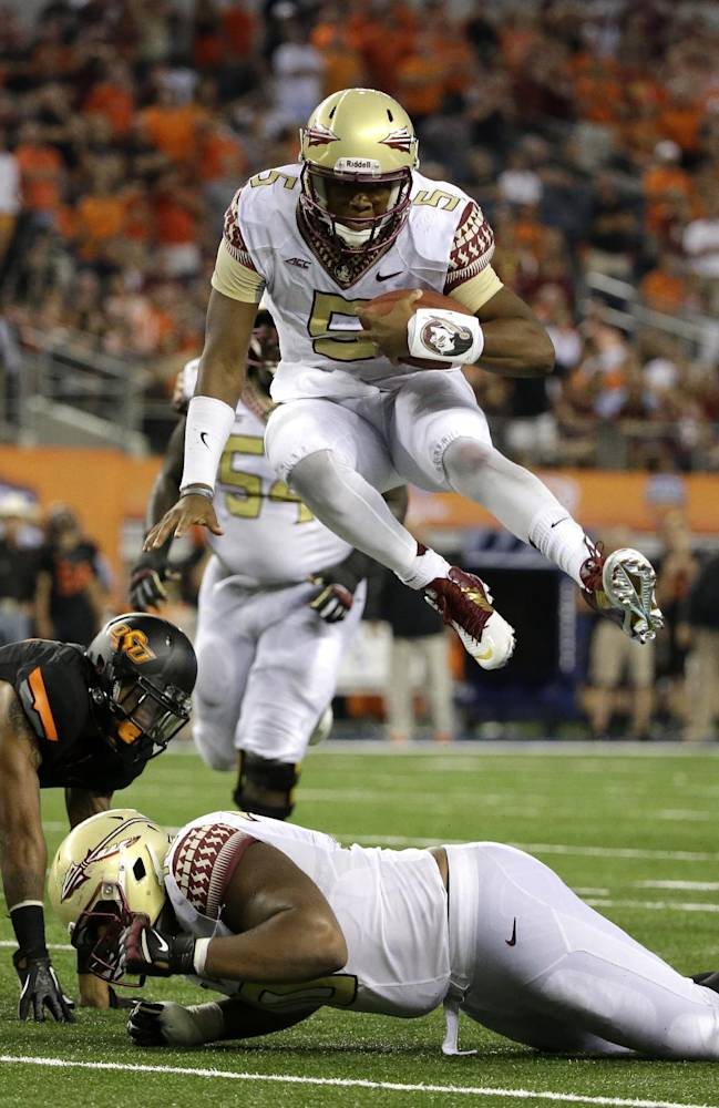 Florida State quarterback Jameis Winston (5) leaps over guard Josue Matias as Oklahoma State safety Jordan Sterns, left, is unable to stop Winston from reaching the end zone for a touchdown in the second half of an NCAA college football game, Saturday, Aug. 30, 2014, in Arlington, Texas