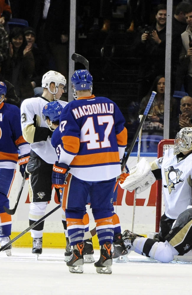 New York Islanders' Kyle Okposo, second from left, celebrates the first of his two goals against Pittsburgh Penguins goalie Marc-Andre Fleury (29) with Thomas Hickey (14) in the first period of an NHL hockey game on Tuesday, Dec. 3, 2013, in Uniondale, N.Y