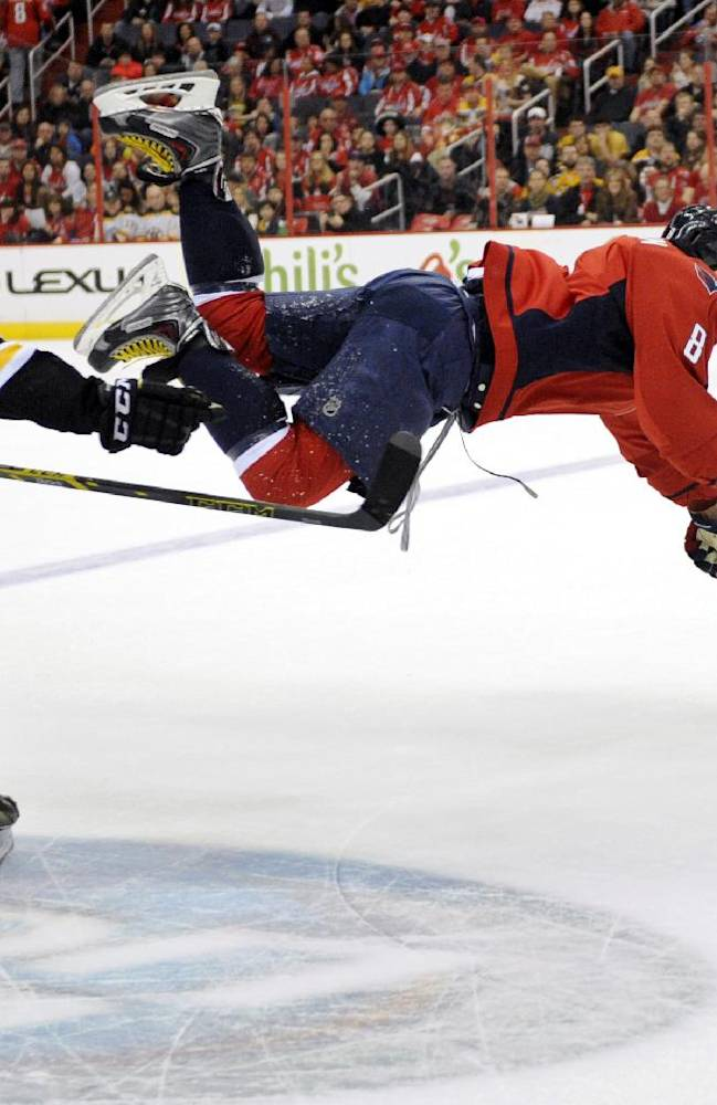 Washington Capitals right wing Alex Ovechkin (8), of Russia, goes airborne after he was tripped up by Boston Bruins center Patrice Bergeron (37) during the first period of an NHL hockey game, Saturday, March 29, 2014, in Washington
