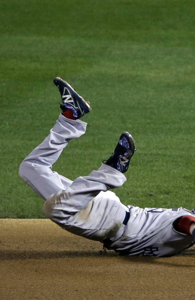 Boston Red Sox's Dustin Pedroia dives for a ball hit by St. Louis Cardinals' Kolten Wong during the eighth inning of Game 3 of baseball's World Series Saturday, Oct. 26, 2013, in St. Louis