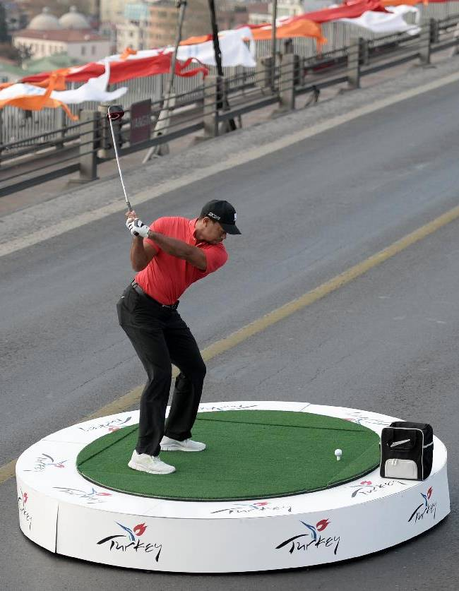 Golf star Tiger Woods of the United States makes a shot from East to West on the iconic Bosporus Bridge that separates the continents of Europe and Asia, in Istanbul, Turkey, Tuesday, Nov. 7, 2013. Woods will compete in the USD7million Turkish Airlines Open in Antalya, Nov. 7-10. (AP Photo)