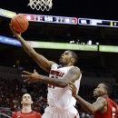Louisville foward Chane Behanan, center, shoots a layup between forward Luke Hancock (11) and guard Kevin Ware (5) during an intrasquad NCAA college basketball scrimmage, Sunday, Oct. 21, 2012, in Louisville, Ky. (AP Photo/Timothy D. Easley)