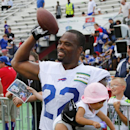 Buffalo Bills running back Fred Jackson (22) holds his daughter, Maecen, as he tosses the ball to his son following a practice at their NFL football training camp in Pittsford, N.Y., Monday, July 21, 2014 The Associated Press