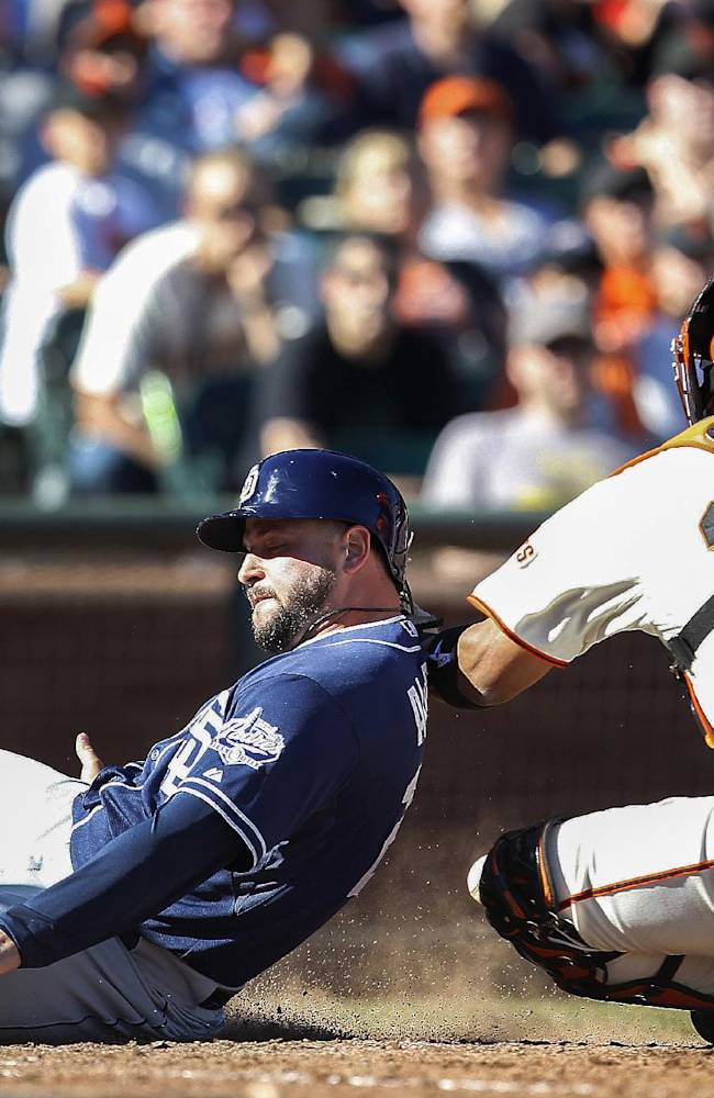San Diego Padres' Yonder Alonso (23) scores a run past San Francisco Giants catcher Hector Sanchez (29) during the ninth inning of a baseball game in San Francisco, Saturday, Sept. 28, 2103. The Padres won 9-3