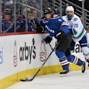 Colorado Avalanche defenseman Erik Johnson (6) and Vancouver Canucks left wing Chris Higgins (20) chase the puck into the corner during the second period of an NHL hockey game on Thursday, March 27, 2014, in Denver The Associated Press