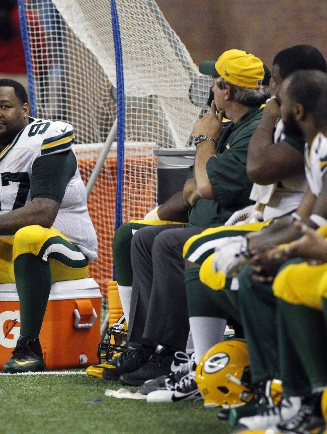 Green Bay Packers defensive end Johnny Jolly (97) and teammates sit during the closing minutes of an NFL football game against the Detroit Lions in Detroit, Thursday, Nov. 28, 2013
