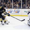 Boston Bruins' Loui Eriksson (21), of Sweden, takes the winning shot on Buffalo Sabres' Jhonas Enroth (1), of Sweden, during overtime in an NHL hockey game in Boston, Sunday, Dec. 21, 2014. The Bruins won 4-3. (AP Photo/Michael Dwyer)