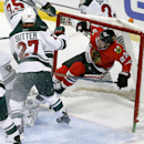 Minnesota Wild center Brett Sutter (27) pushes Chicago Blackhawks right wing Kris Versteeg (23) into the net, during a Blackhawks' power play during the second period of an NHL hockey game Tuesday, Dec. 16, 2014, in Chicago The Associated Press